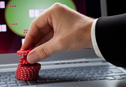 Player placing chips on a laptop which shows an online casino