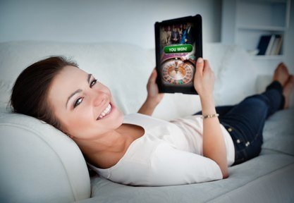 Happy woman lying on couch and gambling on tablet at home in living room